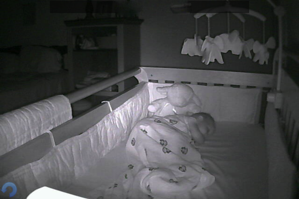 J sleeping on his side in the crib