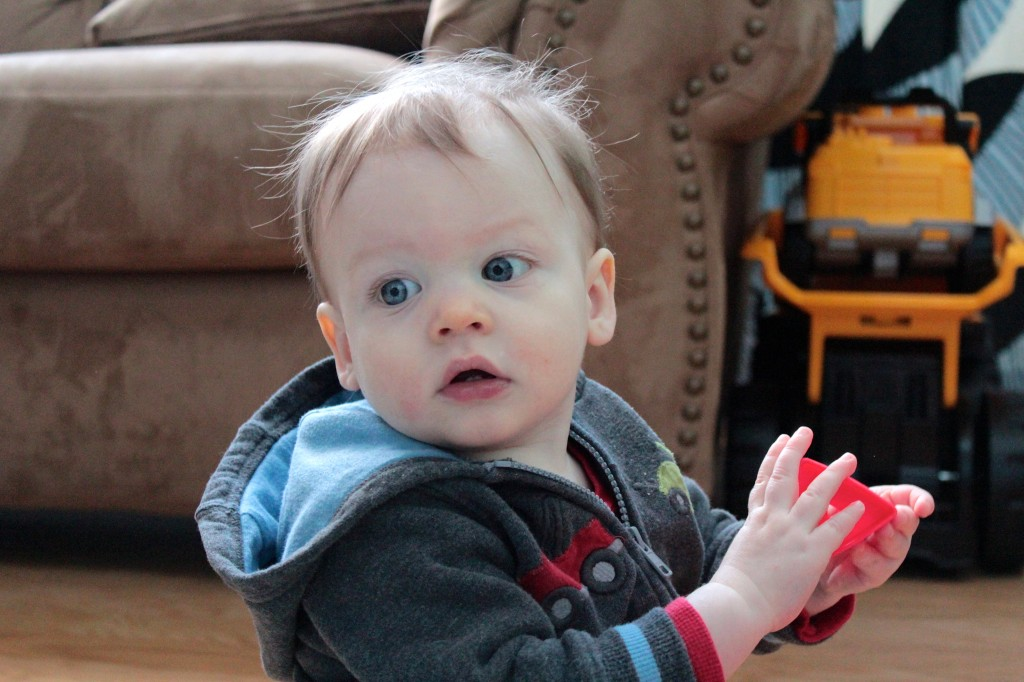 J holding a red block at 13 months